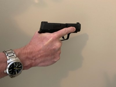 Finger held on slide of gun